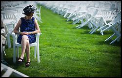 A Racegoer sits in the Grandstand  at Royal Ascot Day 2-Racing Fans<br /> Ascot, United Kingdom<br /> Wednesday, 19th June 2013<br /> Picture by Andrew Parsons / i-Images