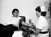 With a possible shortage of blood looming over the St Patrick's weekend, Irish rugby international Tony Ward leads an awareness campaign by donating blood at Pelican House, Mespil Road, Dublin. It clearly doesn't hurt a bit, as Tony chats with Nurse Barbara Maguire during the donation.<br /> 16 March 1984