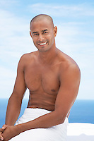 Man sitting with towel round waist smiling half length ocean behind