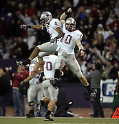 Washington States' Brandon Gibson, left, celebrates with quarterback Alex Brink after Brink threw a 41-yard touchdown during the first quarter in the annual Apple Cup college against Washington, in Seattle, on Saturday, Nov. 24, 2007. (AP Photo/Kevin P. Casey)