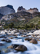 At early sunrise under the Horns, a stream flows into Lago (Lake) Nordenskjold, at Albergue Los Cuernos, a refuge (hut) in Torres del Paine National Park, Chile, Patagonia, South America.