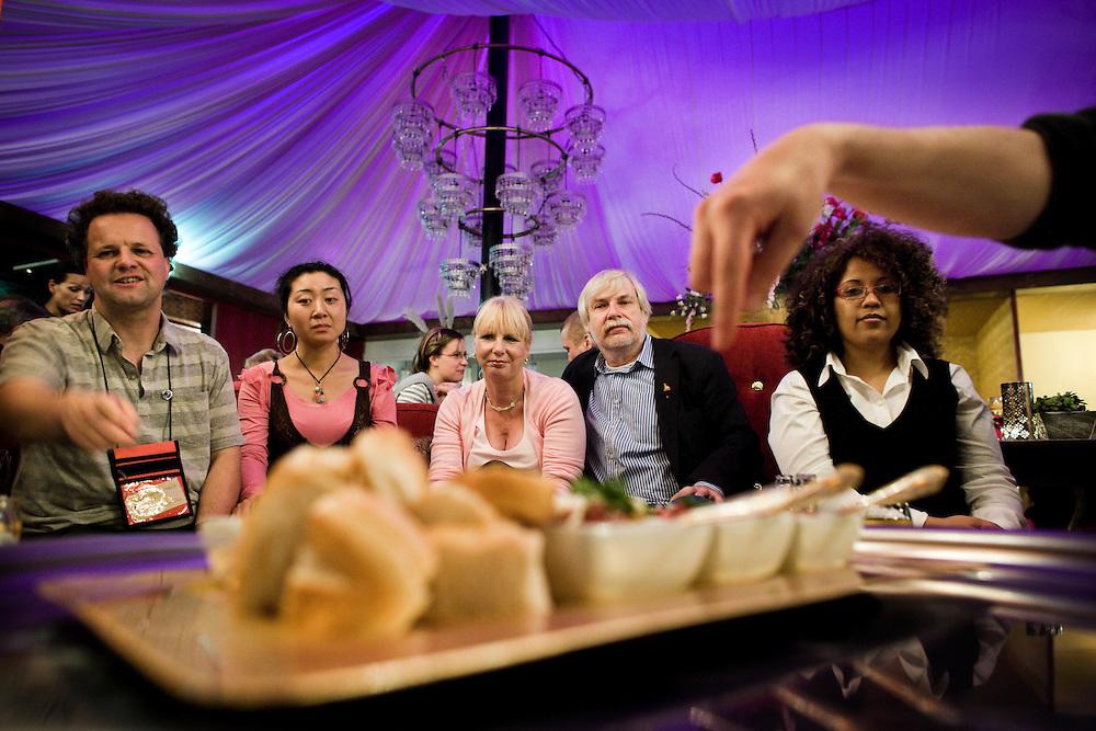 Nederland. Rotterdam, 12 oktober 2007.<br /> De Grote Oversteek, deelnemers in restaurant Obba aan de Hillelaan. Uitleg over de hapjes.<br /> Op vrijdag 12 en zaterdag 13 oktober 2007 vindt op Rotterdam-Zuid de Grote Oversteek plaats. Noord ontmoet Zuid en Zuid ontvangt Noord. Rotterdam Zuid is bij veel Rotterdammers van de noordkant onbekend terrein. Een select gezelschap van Noordelingen krijgt de kans om &eacute;&eacute;n nacht te logeren bij Rotterdammers op Zuid. Zij zullen het zuidelijk deel van de stad heel intens en op de huid beleven. Gastheren en -vrouwen trekken met hen Zuid in en laten hen hun woonomgeving en favoriete plekken beleven.<br /> Voor dit project zijn gastgezinnen gezocht in Charlois, Feijenoord en IJsselmonde, die graag hun Zuid willen laten zien. Die &eacute;&eacute;nmalig hun huis, hart en haard willen openstellen voor een logee uit Noord. <br /> Vanaf 19.00 uur gaan logeerder en gastgezin op ontdekkingstocht langs &lsquo;lekkere&rsquo; plekken op Zuid. Op tenminste drie verschillende eetplekken staat een gerecht klaar. Daarna nemen de gastheren en &ndash;vrouwen hun logee mee naar huis om te verhalen, slapen en de volgende dag samen te ontbijten.<br /> Foto Martijn Beekman <br /> NIET VOOR TROUW, AD, TELEGRAAF, NRC EN HET PAROOL