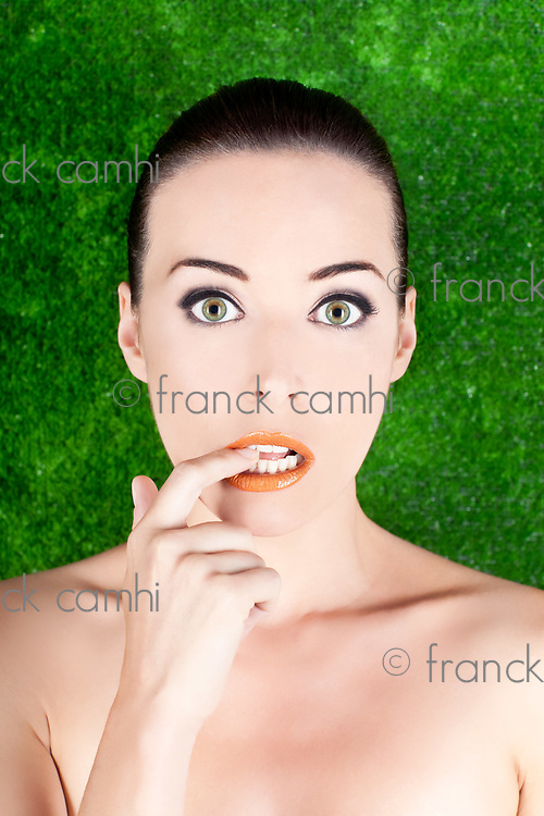 Closeup portrait of a beautiful nervous woman biting her finger isolated on green