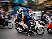 25 DECEMBER 2017 - HANOI, VIETNAM: People on a motorscooter navigate traffic in the Old Quarter of Hanoi.     PHOTO BY JACK KURTZ