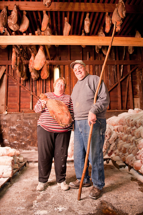 Couple hanging salted hams in shed