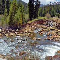 Lake Creek Flowing along Independence Pass, Colorado <br /> Lake Creek follows your journey for about 12 miles along Highway 82 and through Independence Pass. During the springtime snow melt, the water rushes dramatically among the boulders and is flanked by fir trees and aspen groves. There are several good hiking trails in this area. Soon this stream disappears in your rearview mirror as you begin ascending while navigating switchback turns and a narrowing road with steep drop-offs.