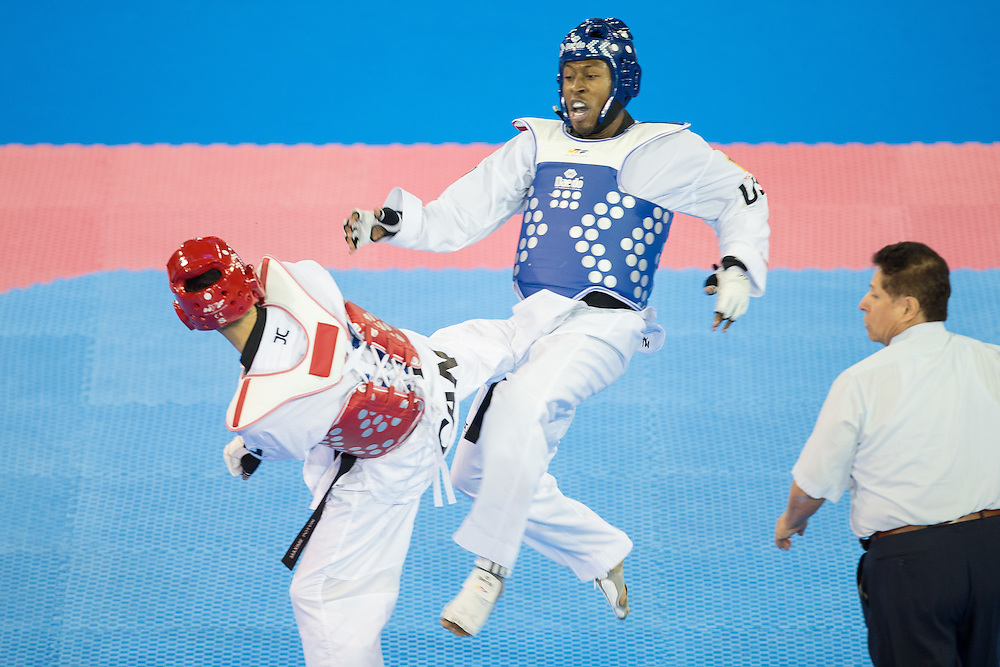 Maxine Potvin (R) of Canada kicks Terrence Jennings of the United States during their semifinal contest in the men's -68kg weight class of Taekwondo at the 2015 Pan American Games in Toronto, Canada, July 20,  2015.  AFP PHOTO/GEOFF ROBINS