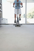 Mature man on exercise bike pedalling low section
