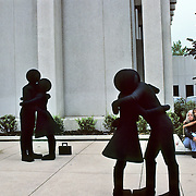 A group called the Pedestrian Project performed at the Busker Fest in Denver.  Here while two couples of the group were huggiing, a young boy emulated them by hugging his mother.   The project consists of several performers wearing entirely black custom-made costumes that are modeled after the generic graphic images of people used on many types of signage. Yvette Helin created the concept in 1989,  More information is available at http://www.yvettehelinstudio.com/Pedestrian_Project/pedhome.html.