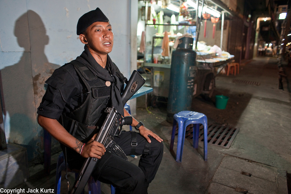 "Sept. 24, 2009 -- PATTANI, THAILAND:  A member of the Thai Rangers, a paramilitary militia trained by the Thai army guard the Pattani night market in Pattani, Thailand. Thailand's three southern most provinces; Yala, Pattani and Narathiwat are often called ""restive"" and a decades long Muslim insurgency has gained traction recently. Nearly 4,000 people have been killed since 2004. The three southern provinces are under emergency control and there are more than 60,000 Thai military, police and paramilitary militia forces trying to keep the peace battling insurgents who favor car bombs and assassination.   Photo by Jack Kurtz"