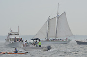 The Argia, a two-masted gaff topsail schooner from Mystic, Connecticut under sail as the Parade of Ships prepares to head out of Niantic Bay, CT toward New London, Connecticut during OpSail2012 CT. Onlookers in a  kayak and in motor boats surround the schooner.