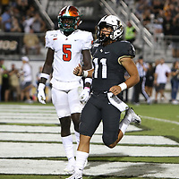 ORLANDO, FL - AUGUST 29: Dillon Gabriel #11 of the UCF Knights runs past Markquese Bell #5 of the Florida A&M Rattlers after throwing his first touchdown pass during a NCAA football game on August 29 2019 in Orlando, Florida. (Photo by Alex Menendez/Getty Images) *** Local Caption *** Dillon Gabriel; Markquese Bell