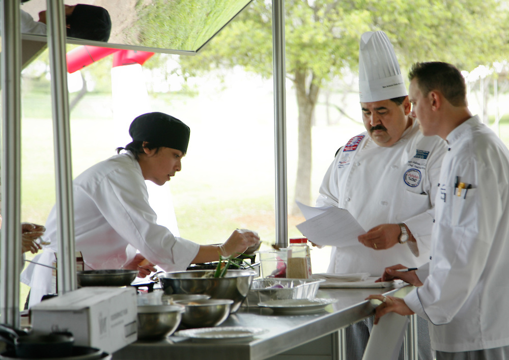 Tim Bagnas (left) is not distracted from creating his entree by chefs Ray Salinas and Yancey Voges (right). High school students from some of San Antonio's high school culinary programs compete for scholarships during the City South Festival Culinary Competition, held at Brooks City-Base, Texas on March 25, 2007. Top prizes included St. Philip's College Culinary School scholarships.  Judging was performed by chefs from the San Antonio Chapter of the Texas Chefs Association.  (Photos/Lance Cheung) ..PHOTO COPYRIGHT 2007 LANCE CHEUNG.This photograph is NOT within the public domain..This photograph is not to be downloaded, stored, manipulated, printed or distributed with out the written permission from the photographer. .This photograph is protected under domestic and international laws.