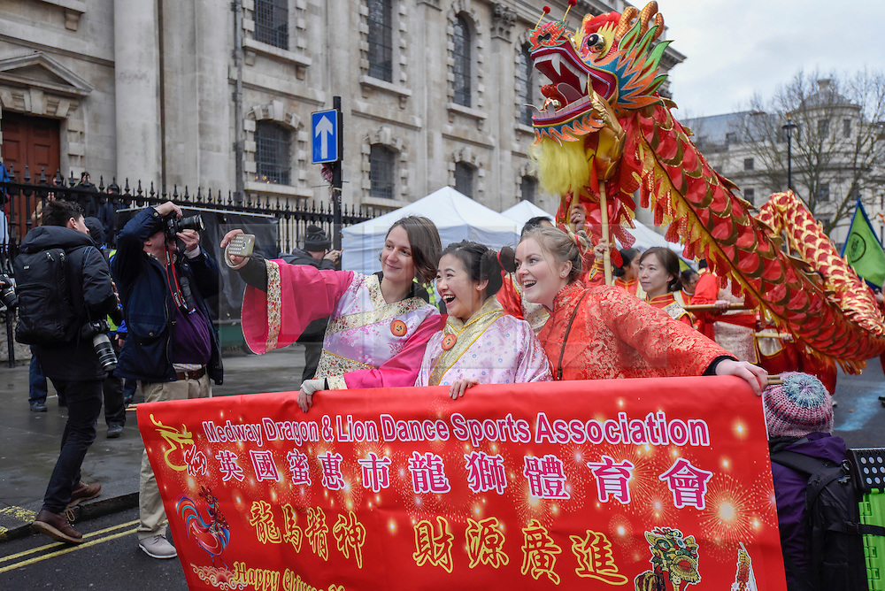 © Licensed to London News Pictures. 29/01/2017. London, UK.   Participants take a selfie as the Chinese New Year parade takes place around Chinatown to celebrate the Year of the Rooster. Photo credit : Stephen Chung/LNP