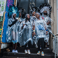 London, UK - 25 August 2014:  revellers protect from the rain during the Notting Hill Carnival in London.