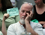 "A person holds up a small sign reading ""health reform now"" at a town hall meeting on healthcare reform hosted by Rep. Mike Coffman (R-CO) in Littleton, Colorado August 12, 2009. REUTERS/Rick Wilking (UNITED STATES POLITICS HEALTH)"