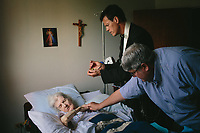 "Tim Reilly reaches out to his mother Johanna Reilly as Father Brendan Gibson gives last rites and the Apostolic Pardon not long after she had suffered a stroke that left her in and out of consciousness. Every Sunday, Gibson visits parishioners who are sick and unable to attend mass. Reilly said he felt great relief to have his mother receive the Catholic indulgence that he believes would keep her out of purgatory. ""If you get the apostolic pardon, you go straight to heaven,"" Reilly said. ""It puts my mind a lot at rest."" Reilly died on Saturday, October 1, 2016. 