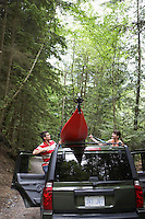 Man tying kayak on car roof in forest