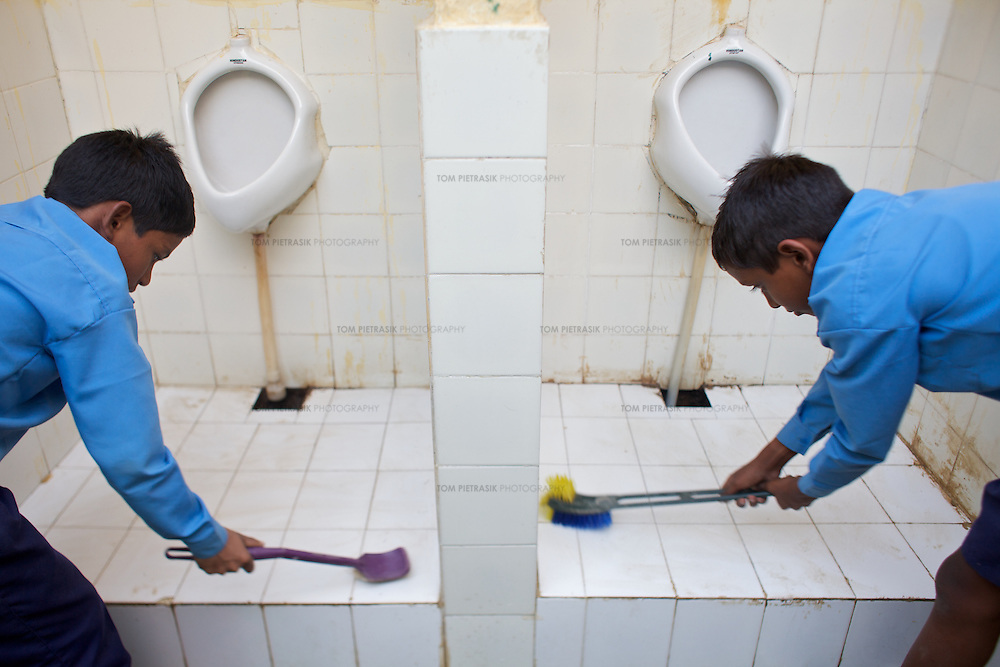 Two pupils at Niyamatpur Khurd primary school clean the boys toilets. The school handwashing area and toilet are adorned with colourful paintings and are an example of the kind of attractive facitilty encouraged by UNICEF...UNICEF and the Uttar Pradesh Government, have identified 36 model Gram Panchayats (local-level village administration) in Mirzapur District. The promotion of good sanitation and hygiene practices in these Gram Panchayats allows them to serve as examples for the remaining areas of the district to emulate. The promotion of hygiene and sanitation includes the construction and painting of school toilet blocks, the construction of individual toilets in households, the digging of garbage pits, recycling waste water and encouraging personal hygiene awareness. ..Only 32 percent of those living in Uttar Pradesh, India's largest state, have access to a toilet. Uttar Pradesh faces many challenges in it's efforts to address this deficiency. UNICEF supports the Uttar Pradesh government's sanitation and hygiene project at both the state and district levels. UNICEF is working to increase the capacity of all of those involved in the sanitation and hygiene project from state-level administrators through to Panchayati Raj (local-level administration) officers and influential individuals, including teachers, who live among rural communities. UNICEF has prioritised the need to communicate the importance of good sanitation and hygiene practice to these communities. The Uttar Pradesh government and UNICEF have focussed their campaign on eight districts (including Mirzapur) with the intention that these serve as models for the remaining 62 districts of the state. UNICEF have identified areas of shortcoming within the government program and proposed solutions. These solutions include the proper training of masons, the provision of rural pans (toilet bowls which require less water per flush) and the identifying of local motivators who champion the program on the ground.