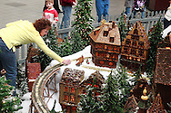 Matthew Busse, 8 of Alexandria, Kentucky watches as Judy Eglian  of Foster, Kentucky adds people to the Huntington Holiday Train display as setup nears completion at the main branch of the Columbus Metropolitan Library in downtown Columbus, Sunday, November 25, 2012..The trains are setup by Applied Imagination on Saturday and Sunday and will run through mid-January.
