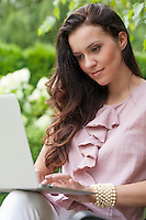 Beautiful young woman using laptop in park