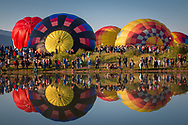 Hot air balloons are reflected in the water as they are inflated during the annual Hot Air Balloon Rodeo in Steamboat Springs, CO.