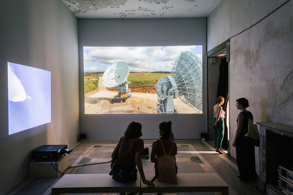 PALERMO, ITALY - 15 JUNE 2018: Visitors watch &quot;Signal Flow&quot; (2018) by documentary director Laura Poitras at Palazzo Forcella De Seta during Manifesta 12, the European nomadic art biennal, in Palermo, Italy, on June 15th 2018.<br /> <br /> Manifesta is the European Nomadic Biennial, held in a different host city every two years. It is a major international art event, attracting visitors from all over the world. Manifesta was founded in Amsterdam in the early 1990s as a European biennial of contemporary art striving to enhance artistic and cultural exchanges after the end of Cold War. In the next decade, Manifesta will focus on evolving from an art exhibition into an interdisciplinary platform for social change, introducing holistic urban research and legacy-oriented programming as the core of its model.<br /> Manifesta is still run by its original founder, Dutch historian Hedwig Fijen, and managed by a permanent team of international specialists.<br /> <br /> The City of Palermo was important for Manifesta&rsquo;s selection board for its representation of two important themes that identify contemporary Europe: migration and climate change and how these issues impact our cities.