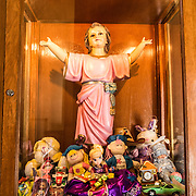 A statue dedicated to children in a case packed with toys that have been donated in the Iglesia de la Santisima Trinidad in Mexico City, Mexico. Iglesia de la Santisima Trinidad translates as Church of the Holy Trinity.