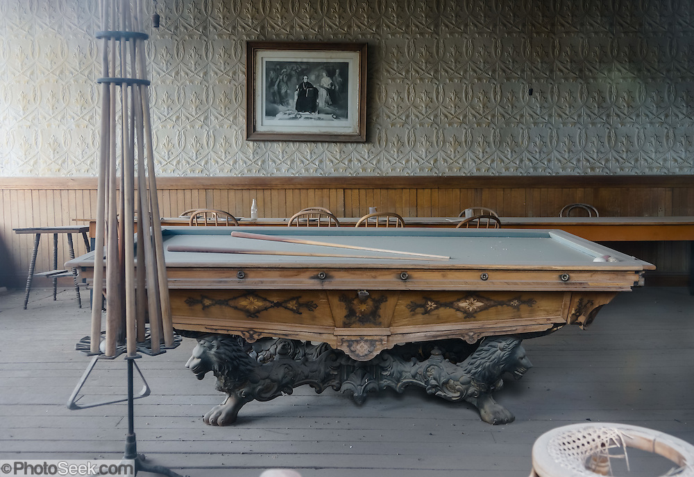"A billiard table collects dust in the Wheaton & Hollis Hotel at Bodie, California's official state gold rush ghost town. In 1885-86, this building served as the United States Land Office. Later, it was the office for the Power Company, then the Bodie Store, and finally the Hotel. Bodie State Historic Park lies in the Bodie Hills east of the Sierra Nevada mountain range in Mono County, near Bridgeport, California, USA. After W. S. Bodey's original gold discovery in 1859, profitable gold ore discoveries in 1876 and 1878 transformed ""Bodie"" from an isolated mining camp to a Wild West boomtown. By 1879, Bodie had a population of 5000-7000 people with 2000 buildings. At its peak, 65 saloons lined Main Street, which was a mile long. Bodie declined rapidly 1912-1917 and the last mine closed in 1942. Bodie became a National Historic Landmark in 1961 and Bodie State Historic Park in 1962."