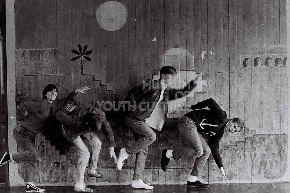Teenagers dance in front of mural, Essex, UK, 1983