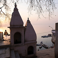 Morning rituals and meditations being performed on the banks of the holy Ganges River in Varanasi, India at sunrise.