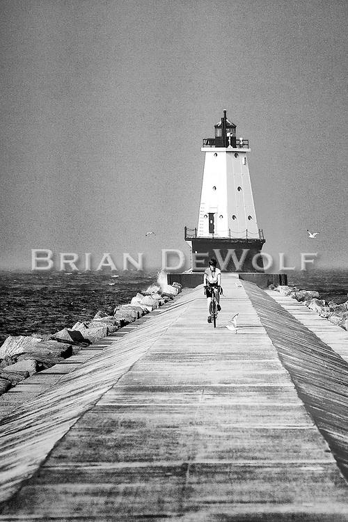 Bicyclist on Luddington, MI lighthouse pier.  Aspect Ratio 1w x 1.5h.