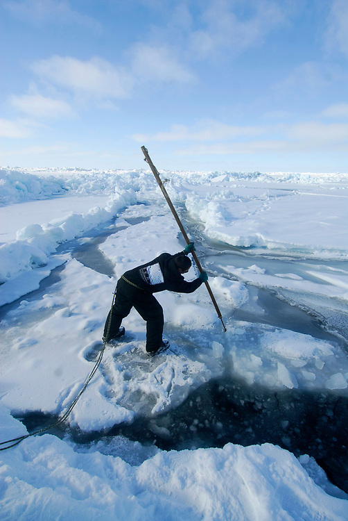 Alaska, Barrow. Whaler at whaling camp on the shorefast ice of the frozen Arctic ocean. Hopson Crew whaling camp. When the ice closed up, the whalers decided dig a hole on thiner ice to see if any marine wildlife would use the hole as a breathing hole. (Model Release)