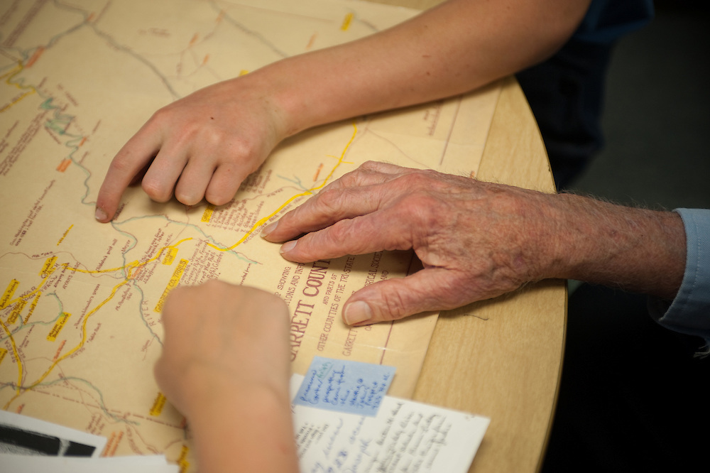 Youth hand and senior hand on a map