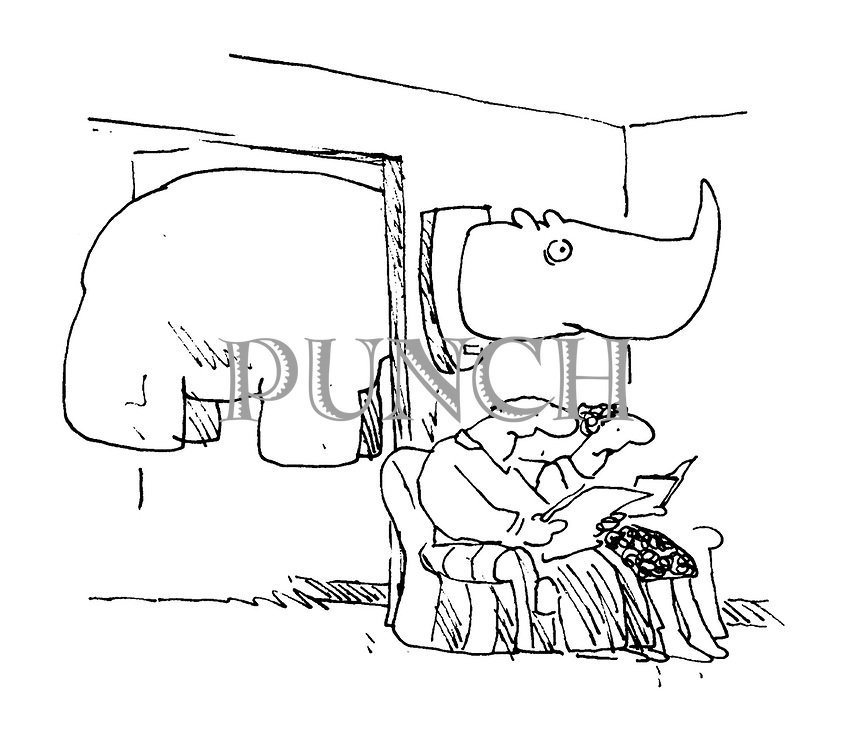 (The stuffed head of a rhinocerus sits on a sitting room wall, while the rest of its body sticks out on the other side of the wall)