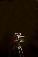 Digital camera and tripod against black background