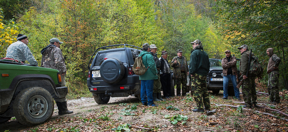 Romanian hunters gathering at their 4WD cars after a driving hunt for Wild boar (Sus scrofa) in the forest area outside the village of Mehadia, Caras Severin, Romania.