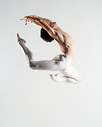 Classical male ballet dancer in white tights jumping in the photo studio on a light grey background. Photograph taken in New York City by photographer Rachel Neville.