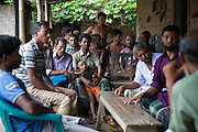 At Borezerdanga village in one of the enclaves near the town of Debiganj a meeting is being held between village elders and men known as 'peace keepers' including Zoynul Hoque, 34, (purple shirt right). Here to discuss the issue of an underage marriage, until a few weeks ago when the enclaves were disbanded the Bangladeshi police had no jurisdiction inside the enclaves so residents relied on peace keepers to sort out problems ranging from illegal logging to land disputes.<br /> <br /> Mr Hoque, despite his young age has been a peace keeper for 10 years owing to him attaining a higher education qualification compared to most who live in the chitmahals.<br /> <br /> On July 31st 2015 the enclaves that formed one of the world's most complicated borders were officially absorbed in to the countries that surrounded them in a land-mark land swap between India and Bangladesh. The people that lived in them will finally receive citizenship.<br /> <br /> Enclaves are small pockets of sovereign land completely surrounded by another sovereign nation. Approximately 160 enclaves, known as chitmahals, exist on either side of the India-Bangladesh border. For 68 years the 50,000 plus inhabitants of these enclaves have lived a difficult existence, stranded from their home nation and ignored by the country that surrounds them. <br /> <br /> In theory even leaving their enclaves is illegally crossing an international border and for decades it has been very difficult for them to receive even the most basic of rights whether education or health. Even the police have no jurisdiction in the enclaves leaving them essentially lawless.
