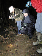 Dawn Dyer (left) checks a photograph of salamanders while Tom Schneider looks on and Dale Dyer (right) holds a flashlight after the release of Spotted Salamanders caught in traps the night before at Sugarcreek MetroPark, Wednesday, March, 19, 2008.