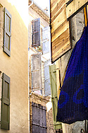 A multitude of shutters in Pézenas, and a deep blue cloth swinging in the breeze.
