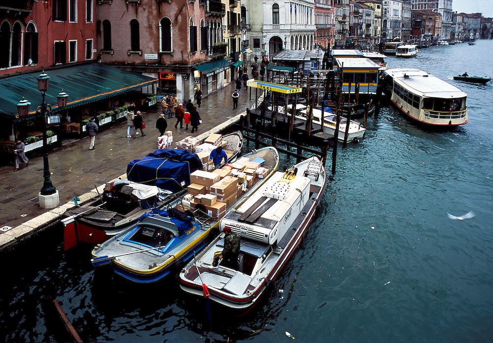 Below Rialto Bridge, Grand Canal, Venice, moored barges and a vaporetto approaching the Rialto vaporetto stop..