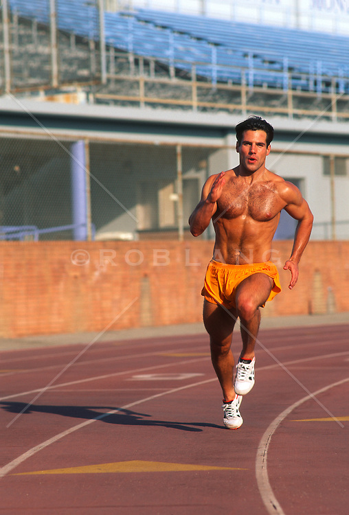 Good looking shirtless man running on a track