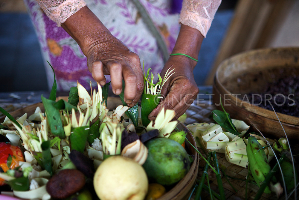 A Balinese woman preparing food-flowers and gifts for a ceremony in Ubud. &copy;Ingetje Tadros<br /> www.ingetjetadros.com