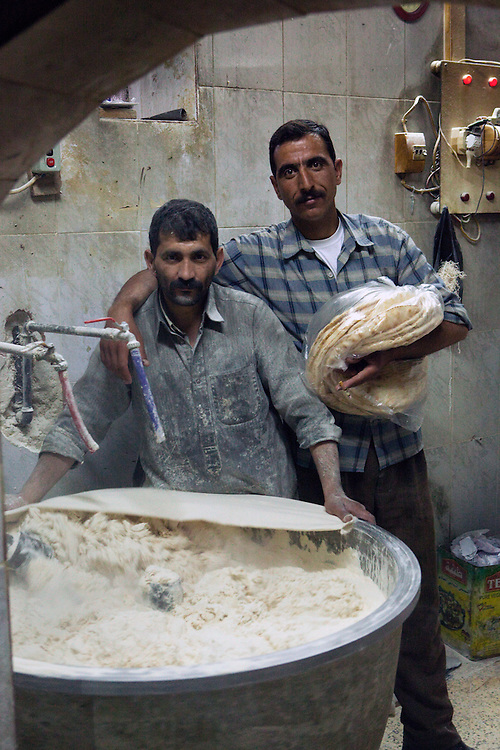 Two men making dough in a small bread factory, which bakes traditional flatbread in the early morning, Aleppo