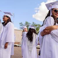 Kimberly Johnson, right, and Tamara Arviso share a hug as they get ready for the Miyamura High School graduation ceremony Friday at Public School Stadium in Gallup.