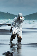 30 JULY 2013 - KOH SAMET, RAYONG, THAILAND:   A worker wipes his face while he walks through oily surf on Ao Prao beach on Koh Samet island. About 50,000 liters of crude oil poured out of a pipeline in the Gulf of Thailand over the weekend authorities said. The oil made landfall on the white sand beaches of Ao Prao, on Koh Samet, a popular tourists destination in Rayong province about 2.5 hours southeast of Bangkok. Workers from PTT Global, owner of the pipeline, and up to 500 Thai military personnel are cleaning up the beaches. Tourists staying near the spill, which fouled Ao Prao beach, were evacuated to hotels on the east side of the island, which was not impacted by the spill. PTT Global Chemical Pcl is part of state-controlled PTT Pcl, Thailand's biggest energy firm.    PHOTO BY JACK KURTZ