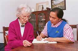 Carer wearing uniform assisting elderly woman to complete pension book,