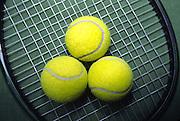 3 yellow tennis balls on racquet head, close-up
