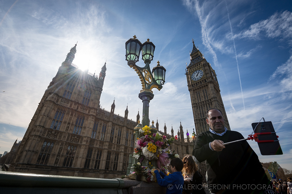 A man takes a selfie in front of Westminster, the Big Ben and the flowers donated to the victim of London terrorist attack